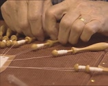 Stock Video Footage of old lady's hands, making bobbin lace, weaving the bobbins - close up