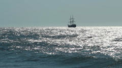 A lone historic sailing ship - caravel - floating on shimmering sea waves Stock Footage