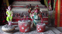 Chinese and Thai religious figurines at street shrine in Macau Stock Footage