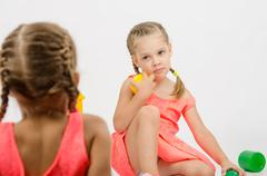 Girl misunderstanding looks at her sister while playing with toys - stock photo