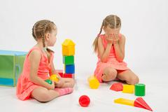 Girl hurt another girl playing with toys - stock photo