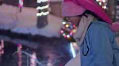 Little Girl Dressed In Santa Hat Looks At Reflection Of Holiday Lights In Water Stock Footage