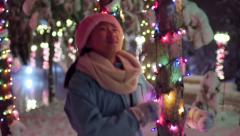 Stock Video Footage of Happy Asian Girl, Wearing Santa Hat, Runs Through Snowy Winter Wonderland