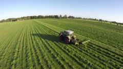 Aerial of tractor mowing grass helicopter view from side of farmer 4k Stock Footage