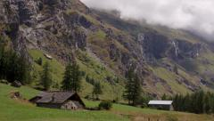 Alpine landscape with chalet, cliffs and meadows Stock Footage