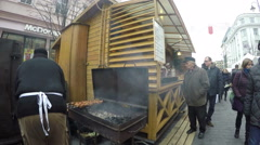 Cook man sack coal into roaster and bake fresh meat in festival Stock Footage