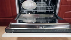 Opened steel cover of built-in dishwasher machine with arranged dishes Stock Footage