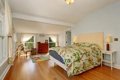 Large spring themed bedroom with hardwood floor. - stock photo