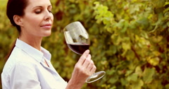 Female winegrower swirling a red wine glass - stock footage