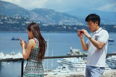 Asian tourists check travel photos at the viewpoint in Monaco. Stock Photos