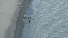Aerial wide shot of two Boys getting their feet wet Stock Footage