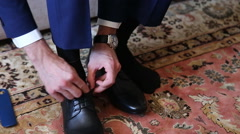 Man puts on shoes. Focus on the laces - stock footage