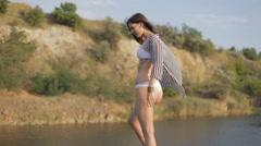 Sexy girl in bikini sunbathing and posing on a rock near the shore of the lake Stock Footage