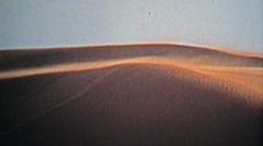 1972: Classic sand dunes attract thrill seekers as the wind picks up. Stock Footage