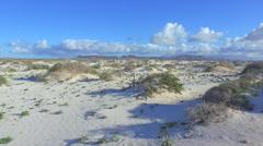 AERIAL: Flying over vast white sand desert towards volcanoes Stock Footage