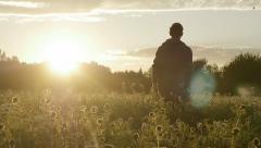 1043 man walkin on a field in sunset Stock Footage