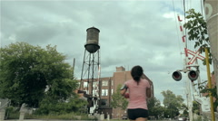 Jogger runs past train tracks followed by cyclist, water tower in background Stock Footage