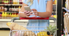 Smiling blonde shopping and using smartphone Stock Footage