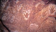 1972: Ancient cave drawings of human hands oldest stencil known to science. Stock Footage
