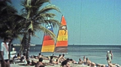 1973: Catamaran sailboats color the beach landscape for tourism rentals. Stock Footage