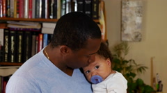 Dad kisses his baby girl on the head, smiles at camera Stock Footage