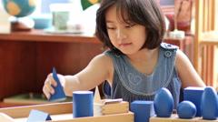 Little Asian girl stacking montessori blocks Stock Footage