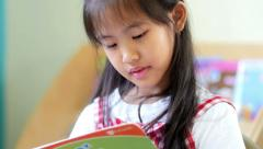 Little Asian students reading book in library Arkistovideo
