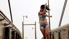 Happy beautiful girl singing and dancing on bridge - stock footage