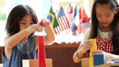 Little Asian girls stacking montessori blocks together Stock Footage