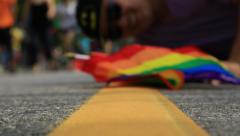 Gay activists laying down on traffic line, waving rainbow flag Stock Footage