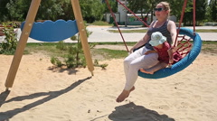 Mother and daughter ride on a swing. Stock Footage
