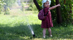 Little girl dabbles with Sprinkler Stock Footage