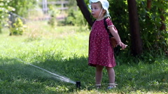 Little girl dabbles with Sprinkler hot day. Stock Footage