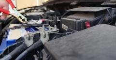 Low angle shot of a person connecting  the booster cables to the car battery - stock footage