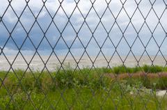 Metallic mesh fence against seashore background Stock Photos