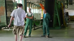 Two Workers in Green Uniform, Standing at The Sheet of Glass,Sheet is Lying Stock Footage