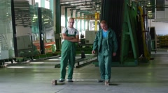 Two Workers in Green Uniform, Are Standing at the Sheet of Glass,Sheet is Lying Stock Footage