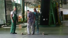 Two Workers in Green Uniform, Holding the Sheet of Glass, Man in Civilian Stock Footage