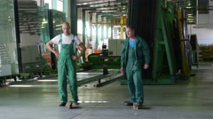 Two Workers in Green Uniform, Boots, Are Standing at the Sheet of Glass, Sheet Stock Footage