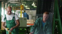 Two Workers in Green Uniform, Put The Sheet of Glass Down, Man in Civilian Has - stock footage