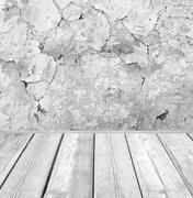 Room interior: grey cracked cement wall with wooden floor Stock Photos