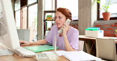 Casual businesswoman on the phone at her desk Arkistovideo