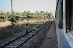 Two Kids Run Along and Follow Train in Burma Stock Photos