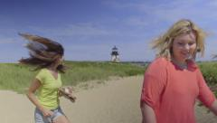 Playful Teen Girls Spin In Circles, Lighthouse In Distance (Slow Motion) Stock Footage