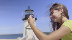 Teenager Takes Photo Of Friends At The Beach Next To A Lighthouse (Slow Motion) Stock Footage