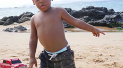 Black toddler playing in sand on a beach - stock footage