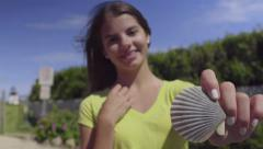 Teenage GIrl Holds Up A Beautiful Scallop Sea Shell (Slow Motion) Stock Footage