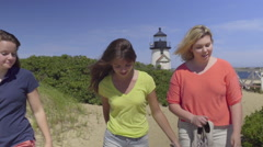 Teenage Girls Chat On Their Beach Walk, Beautiful Lighthouse Behind Them Stock Footage