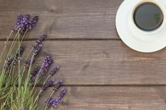 Lavender and cup of coffee on the wooden desk - stock photo