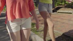 Girls Walk Around Neighborhood, One Balances On Line, Other Balances On Curb Stock Footage